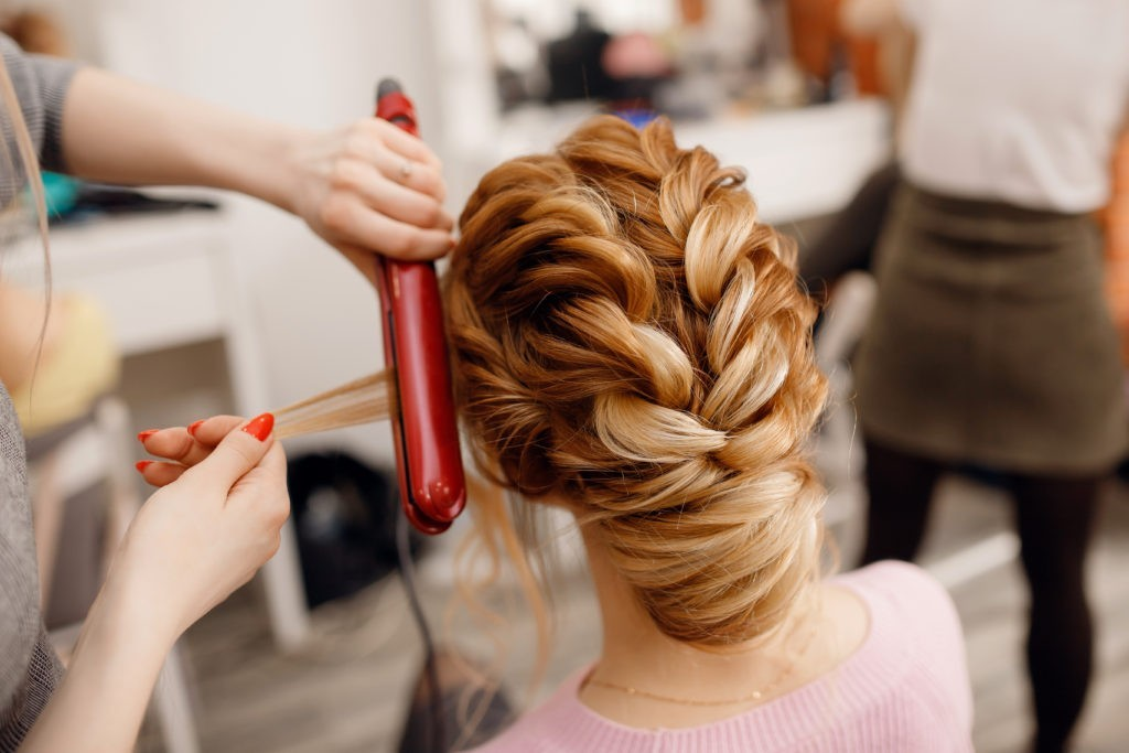 Woman curling her clients up do hair style